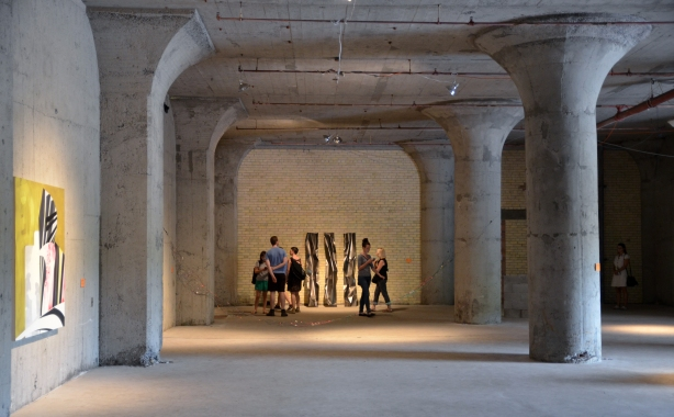 a group of people looking at a piece of art.  They are in a large open space that once was a factory.  Concrete and brick walls.