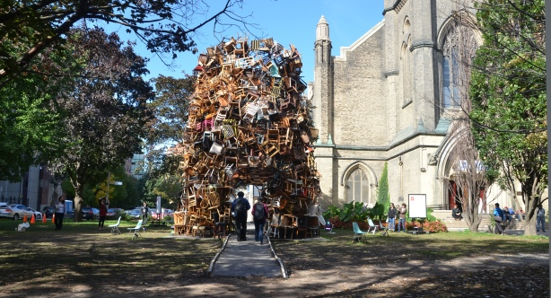 a large pile of chairs sits in front of a church