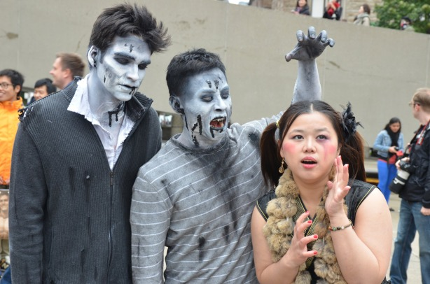 Three people - two grey zombies and a young Asian woman who is pretending to be scared of the zombies