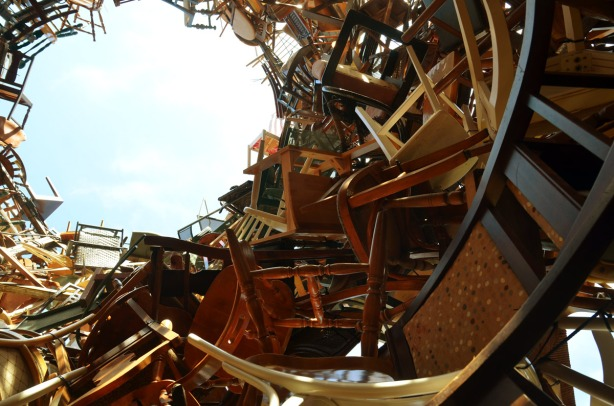 A hollow pile of chairs about thirty feet high.  The photo is taken from inside the pile.  The sky can be seen in the photo.