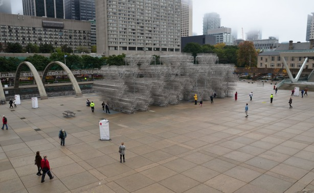 Nathan Phillips Square on a grey and foggy morning.  There are a few people in the square who are looking at the large art installation that involves a structure made from more than 3000 bicycles