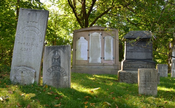 four old tombstones in a cemetery