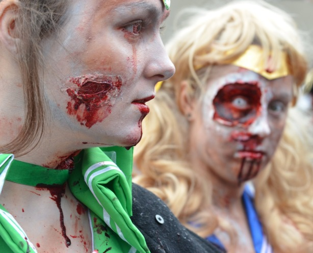 two woman dressed up like zombies.  The woman in the foreground has blood dripping off her chin and down her neck.  The woman in the background has a large ugly facial wound