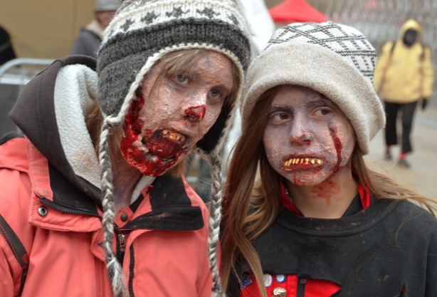 Two girls wearing woolly hats and very ugly fake teeth.  THey have lots of blood on their chinslots of b