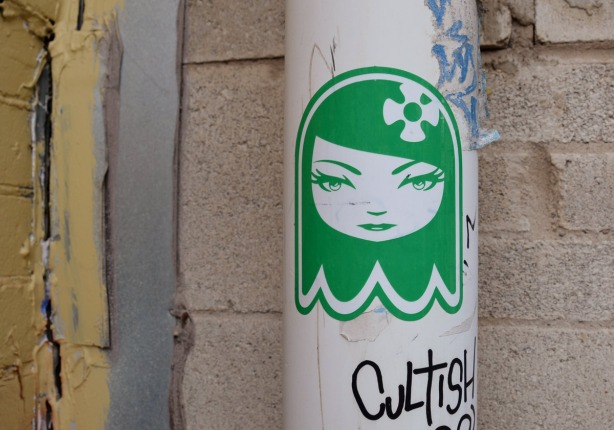 A green and white sticker of a woman's head, stylized.
