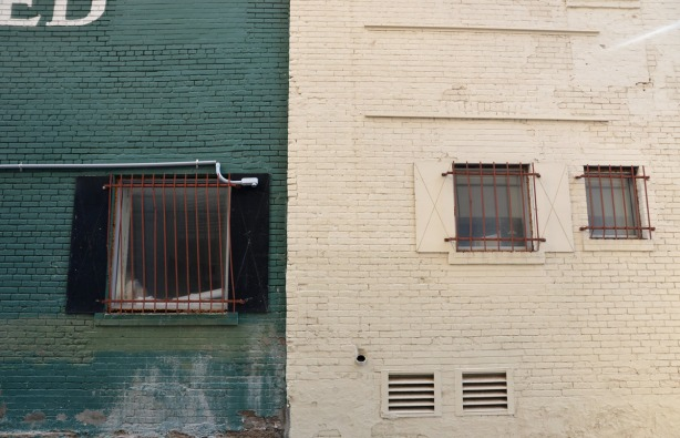 A wall where part is painted dark green and the other part is off-white.  There are three windows, each window has a metal grate over it.