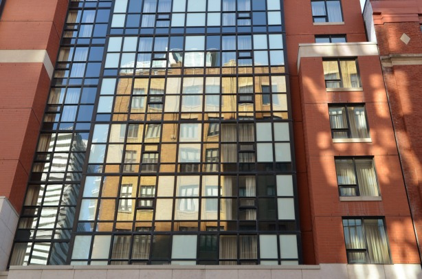 blue sky and a yellow brick bulding are reflected in the many windows of a hotel
