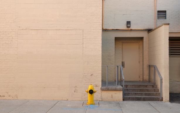 a pinkish coloured wall with a yellow fire hydrant in front of it.  There is also a door and some grey steps on the right side of the picture
