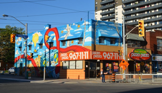 A Pizza Pizza store at the northeast corner of an intersectoin has been painted with a large, colourful mural. All possible surfaces have been painted.