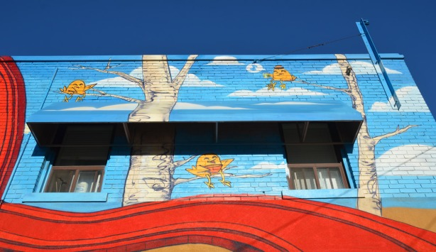 part of the mural by uber 5000 showing three uber chickens sitting on tree branches. This part of the mural is on the second storey and it includes the awning over a couple of windows.