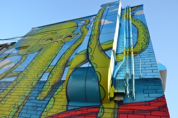 A giant green octopus covers most of the back of the two storey building including the heating vents.