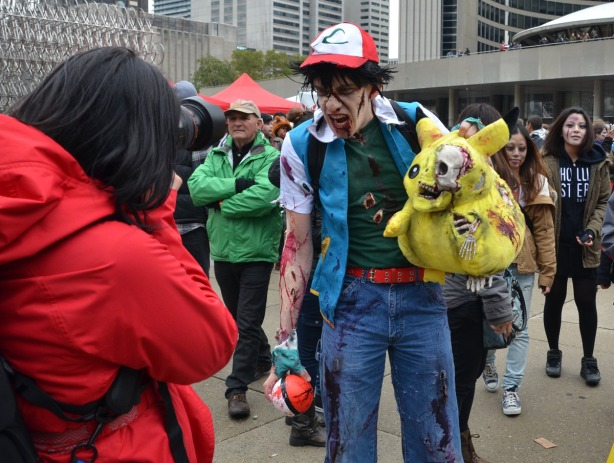A zombie holding a large yellow Pokemon zombie.  He is screaming at a photographer