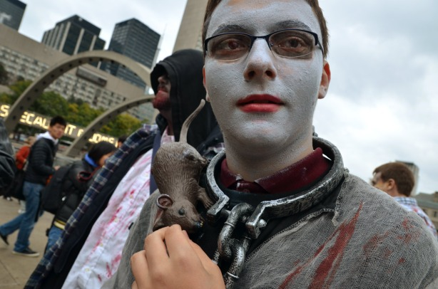A man with white makeup on his face, a chain around his neck and a plastic rat on his shoulder.