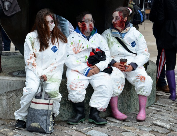 three zombies dressed in white coveralls, sitting by The Archer sculpture in Nathan Phillips Square