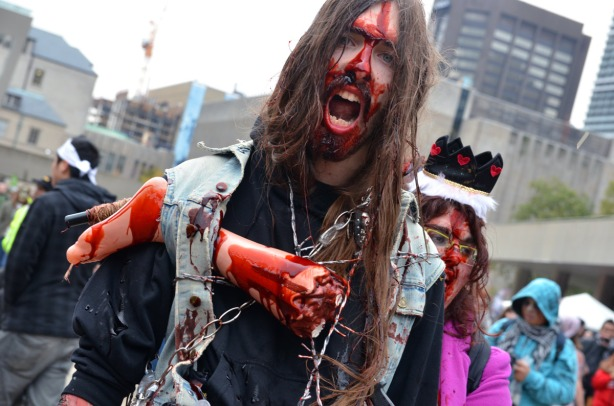 A man with very long hair, a moustache and a beard with blood running down his face.  A fake leg is attached to his shoulder.  and he has chains around his neck