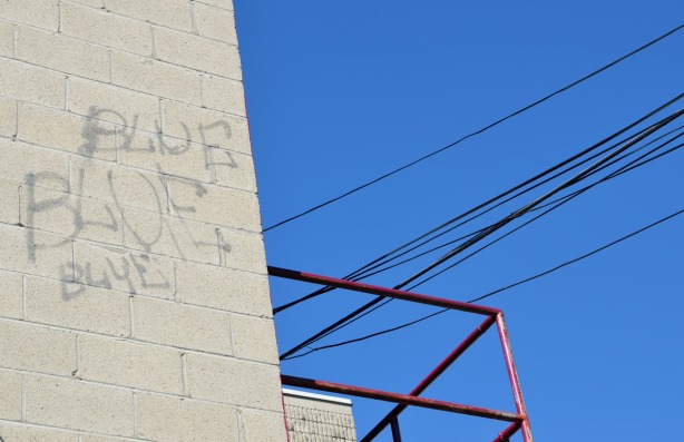 Concrete block wall with the words blue, blue, blue written on it.  The sky behind is very blue.