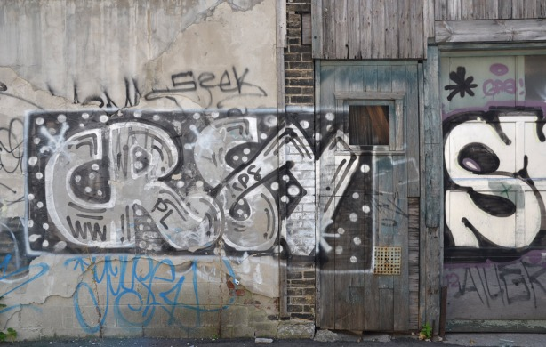 crsy tag on an old grey wood garage in an alley