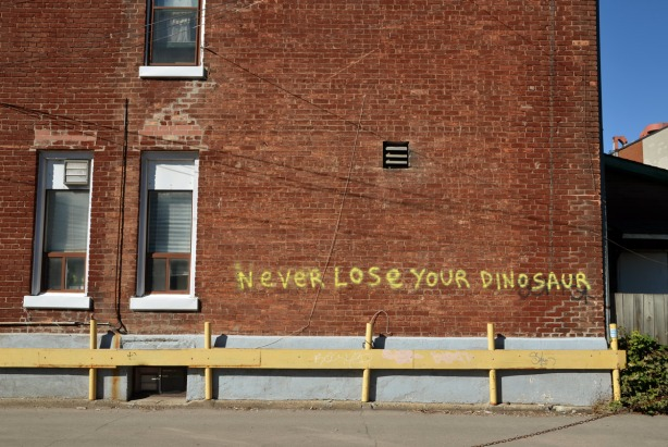 The words, Never lose your dinosaur, are written in large yellow letters on the side of a red brick house.
