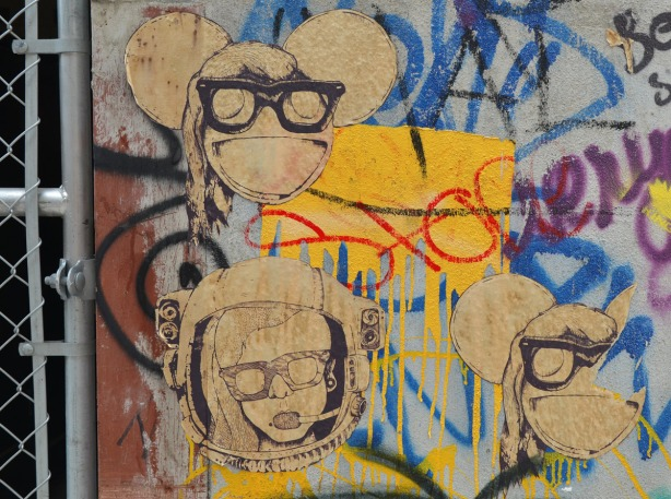 a brown and black set of posters/stencils of three heads.  Two are the same - they look like heads with big ears and they are wearing very big sunglasses.  The third looks like a woman in a helmet like the kind an astronaut might wear.