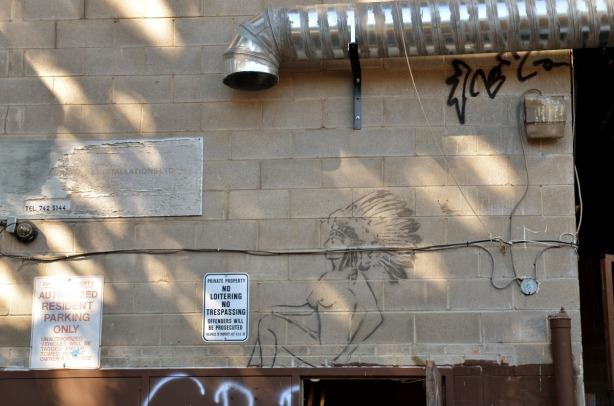 graffiti image of a naked woman who is wearing an Indian feather headdress