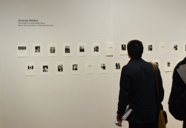A man looking at a series of small black & white prints in an art gallery