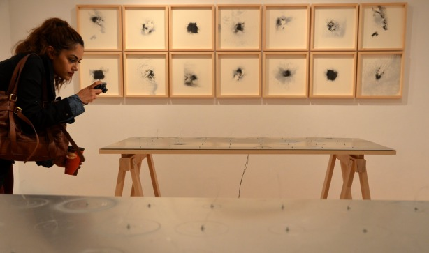 A woman is taking a picture of an art installation that is flat on a table.  Twelve black & white framed prints are on the wall behind her.