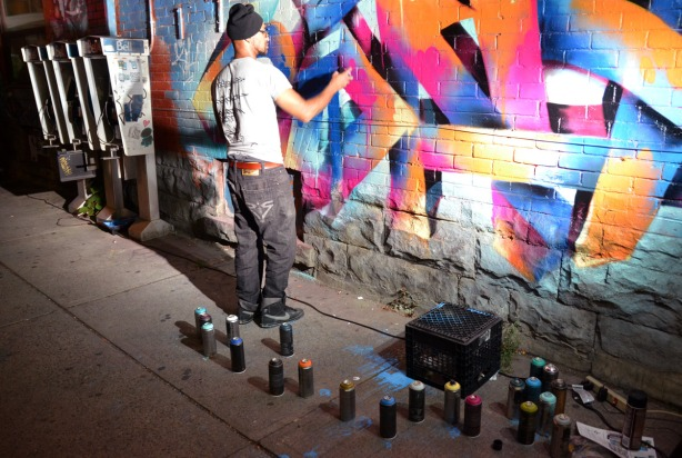 A man is spray painting a piece of street art using aerosol cans of paint