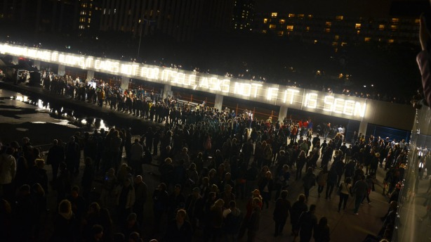 Crowds, at night.  Light is provided by fluorescent lights that spell out a short poem.
