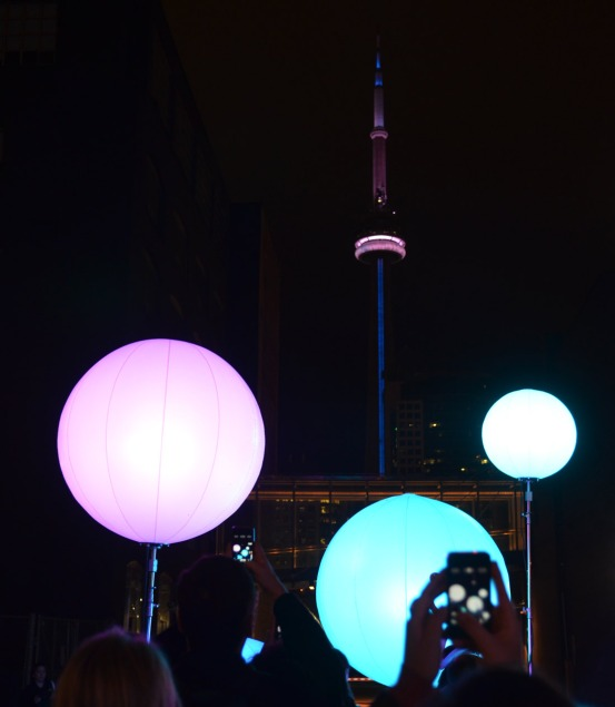 The CN tower, with pink and blue lights, is in the background.  In the foreground are people taking pictures with their phones.  In the middle ground are a number of pink and blue lit spheres