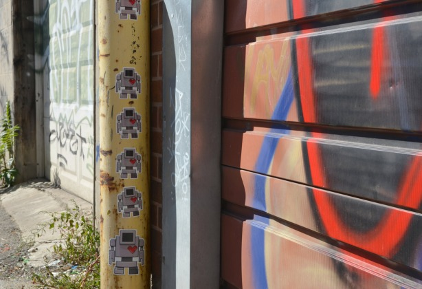 A line of robot stickers on a short yellow pole in an alley