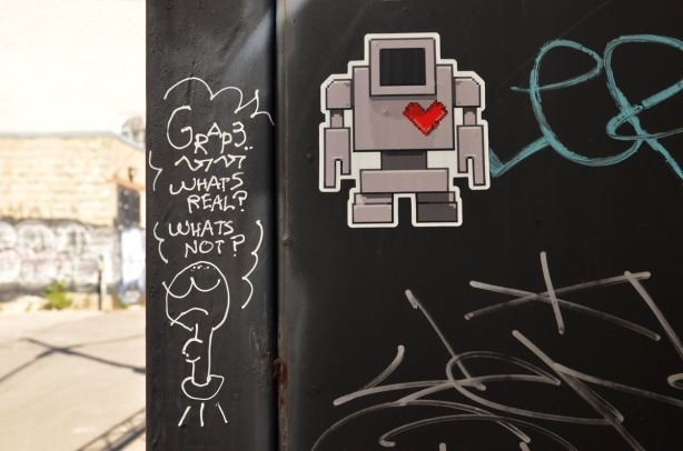 Black wall with a robot and heart sticker.  Someone has written the words, what's real?  what's not?on the wall as well