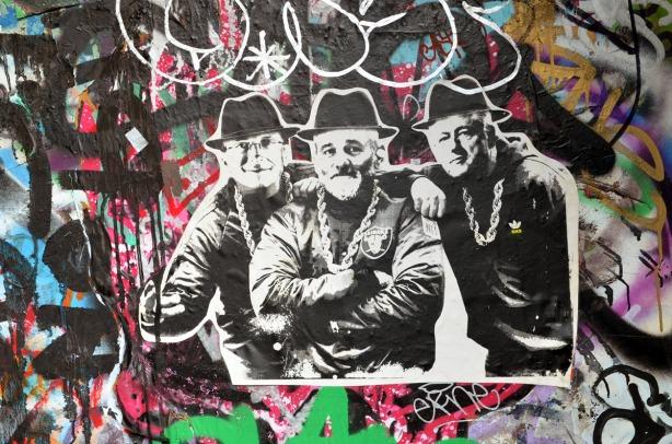 a paper graffiti of Bill Gates, Bill Murray and Bill Clinton on a graffiti covered door