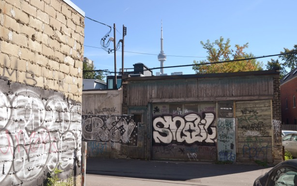 buildings in an alley that have graffiti on them.  the CN Tower is in the background