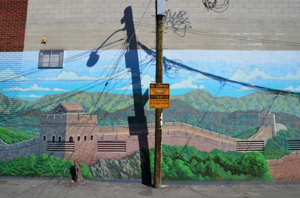 A mural of the Great Wall of China has been painted on the side of a building.  There is a hydro pole in front of it with a sign that says no dumping.