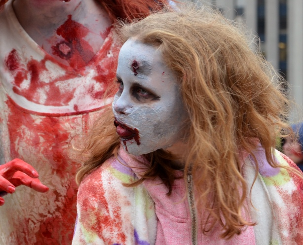 a girl with red frizzy hair who has white makeup on her face and a bloody mouth