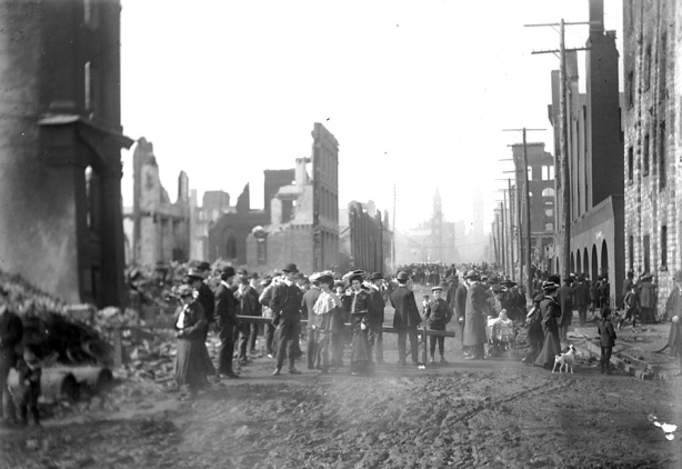 Historical photo of Bay street after the 1904 fire in Toronto.  There are people on the street.  The street is all mud.  There are many burned out buildings on both sides of the streets.  Brick facing of two to four storey buildings is all that remains.
