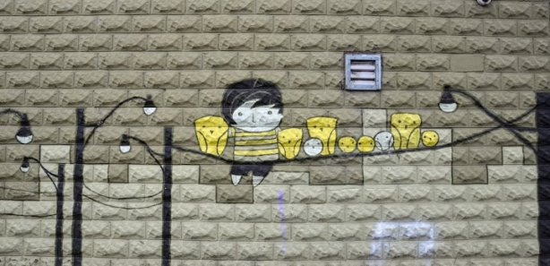 street art on a textured concrete wall showing stylized yellow birds sitting on a telephone wire.  A boy is sitting with them.