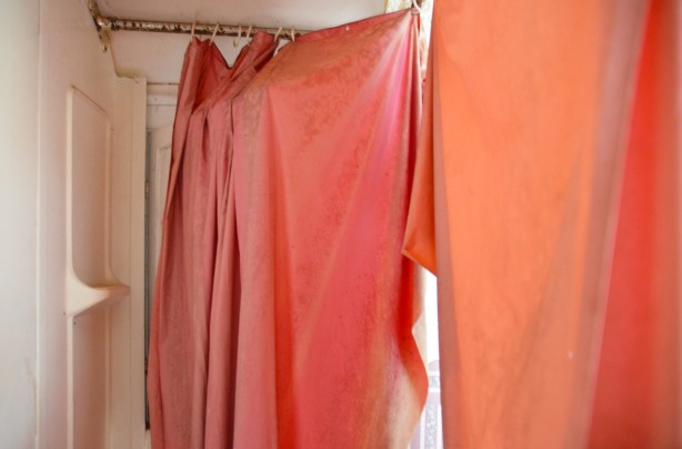 A pink shower curtain that is loosely hanging from the shower curtain rod.