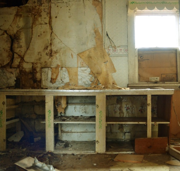 one wall, interior, of a kitchen in an abandoned building.  The window is half boarded up.  The cupboard doors are missing.  The wallpaper is almost all peeled off.  It is filthy.
