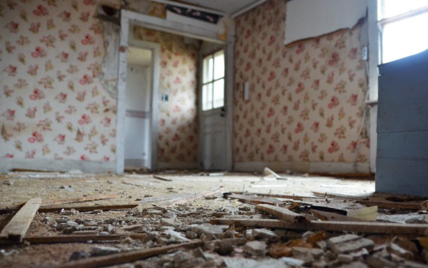 Building materials (cement, wood, bits of ceiling) lie on the floor in the foreground of the photo.  The front door is in the background.  This is probably the livingroom.  Red floral wallpaper is on the walls.