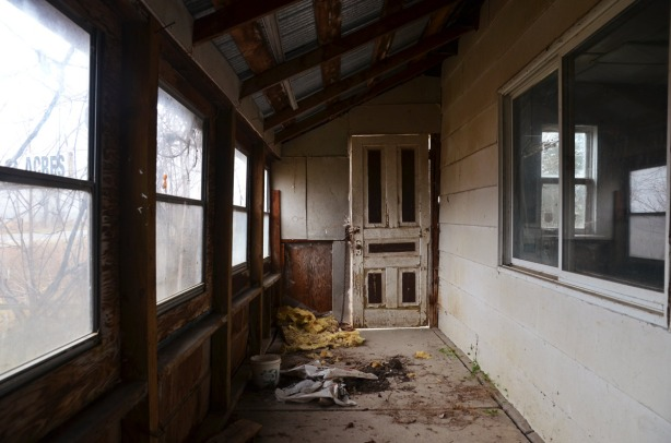 The interior of the front porch room of an abandoned house.  There is lots of debris on the floor, no curtains on the windows.
