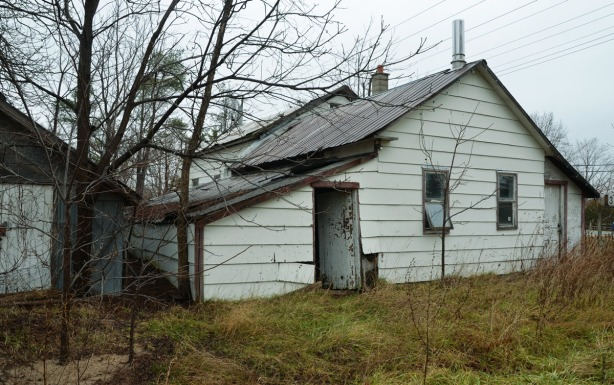 Side of a white clapboard house.  An old door is open.  The house has a metal roof.  There is a blusih grey garage (or shed) behind the house.