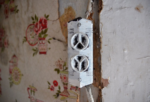 An old electical socket (outlet) that has been painted white.  The wires leading to it are a bit frayed.  It is on a wall with old wallpaper on it.  The wallpaper has red flowers on it.