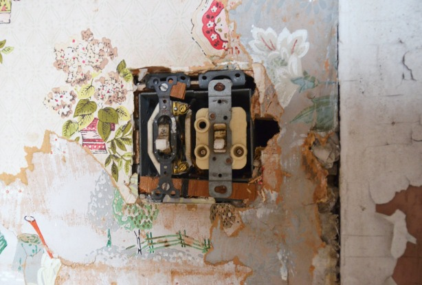 A double light switch that has lost its cover plate, on a wall.   The wall paper around it has been torn in such a way that 3 layers of different floral paper can be seen.