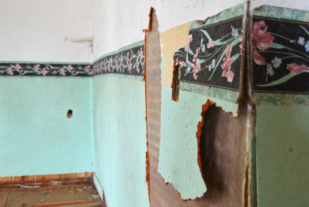 The light teal coloured wallpaper is falling apart on an interior  wall.