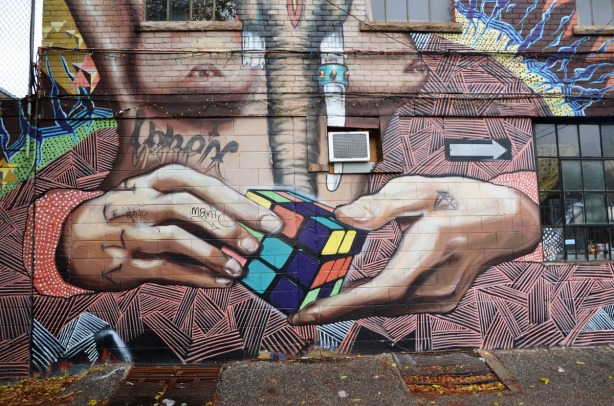 mural showing two large hands hold a Rubik's cube