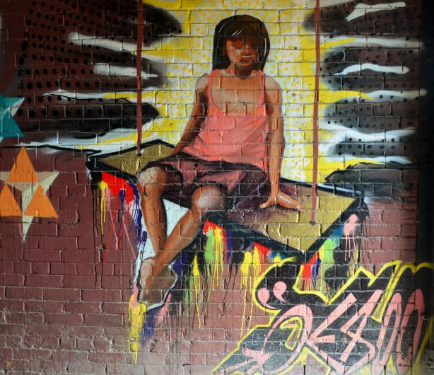 Street art picture of a girl with long black hair, brown shorts and a pink top, sitting on a large swing.