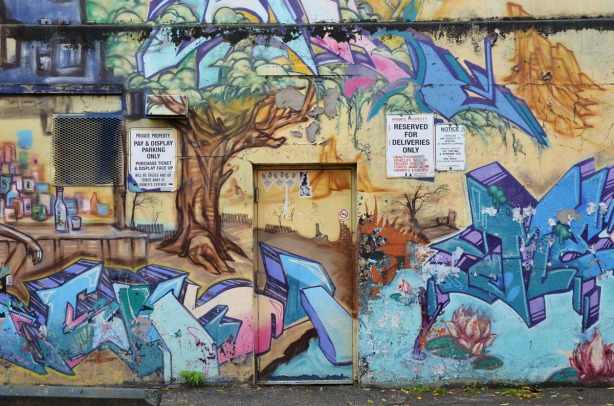 part of a mural on a wall.  There is a door in the middle.  Part of the mural shows a large tree with a brown trunk and multicoloured leaves.