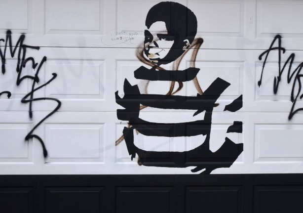 A graffiti picture of a boy who is wearing a black and white striped sweater.  Shown from the hips up.  His hands are on his hips.  It is on a white garage door.