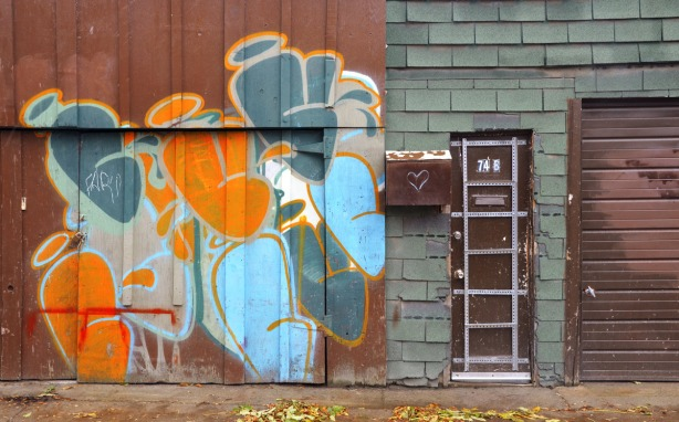 brown garage door, brown front door and rusty brown mail box.  On the garage door is a piece of street art with orange and blue blobs.  The front door is decorated with a grid made of metal strips.